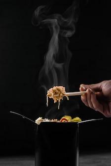 Gotowanie na parze gorącego ryżu w pudełku woka na czarnej powierzchni