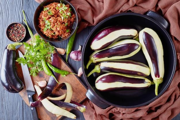 Gotowanie nadziewanych bakłażanów, bakłażanów z mielonym mięsem wołowym, pomidorami i cebulą. składniki na drewnianym stole, widok z góry, leżał płasko