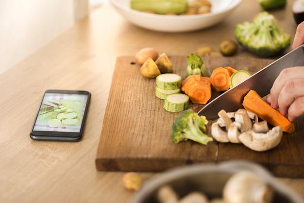 Gotowanie online lub nauka gotowania. człowiek przygotowuje wegańskie danie gotowane na parze warzywa oglądając przepis w internecie za pomocą smartfona