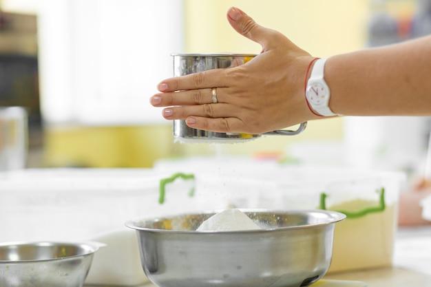 Gotowanie pieczenie. kucharz przesiewa mąkę