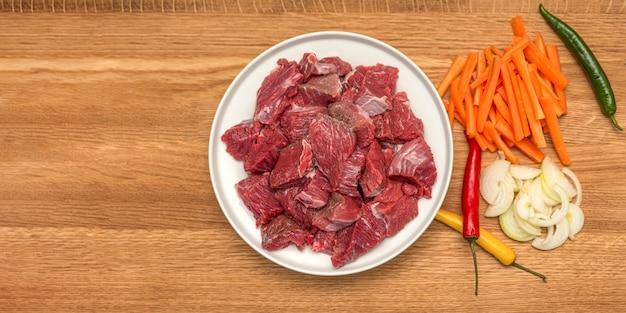Gotowanie pilaw w kotle, przepis na prawdziwy pilaw. składniki do gotowania pilaw na drewnianym tle. cebula, papryka, marchewka, mięso mielone leżą na drewnianej desce do krojenia. gotowanie pilaw w domu.