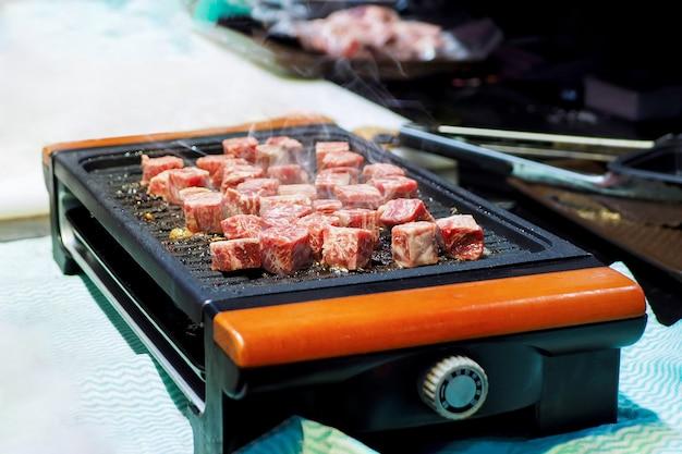 Gotowanie pokrojonego w kostkę stek na żelaznym gorącym talerzu. grillowanie pokrojonej w kostkę wołowiny. grill mięso stek grill.