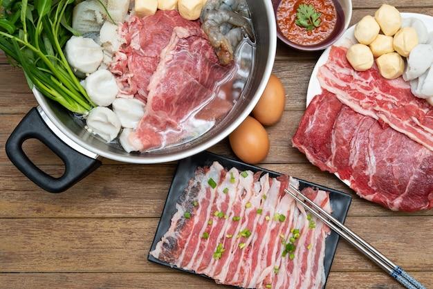 Gotowanie potraw poprzez umieszczenie mięsa wołowego, wieprzowiny, jajek i warzyw w gorącym garnku, aby zrobić sukiyaki lub shabu w japońskiej restauracji bufetowej shabu
