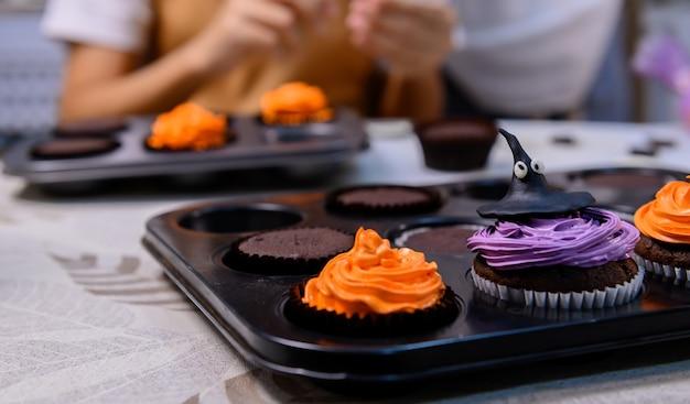 Gotowanie pysznego domowego ciasta i dekorowanie babeczki na świąteczny halloween. przygotowanie i mieszanie składników na słodki deser spożywczy w kuchni w domu.