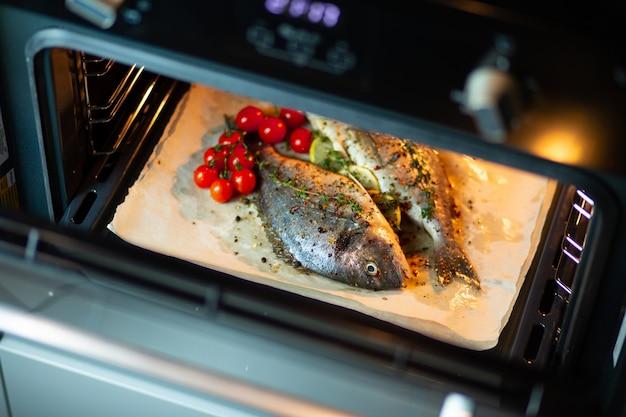 Gotowanie ryb w piekarniku. gotowanie dorado z pomidorami koktajlowymi i ziołami na pergaminie w piekarniku.