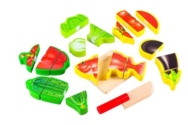 Gotowanie ryb. zestaw warzyw, ryb, noża i deski do krojenia. z edukacyjną zabawką montessori. białe tło. zbliżenie.