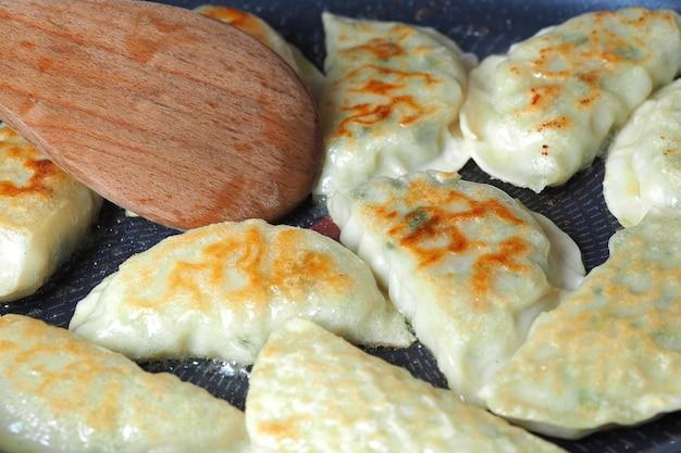 Gotowanie smażone pierogi z bliska na patelni. chińskie jedzenie z gorących par, na rustykalne drewniane tło.