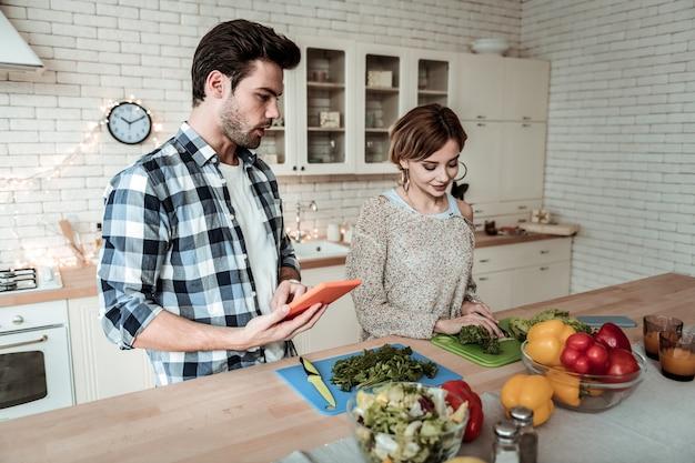 Gotowanie śniadania. młoda ładna kobieta z dużymi kolczykami wygląda na zadowoloną podczas cięcia zieleni w kuchni
