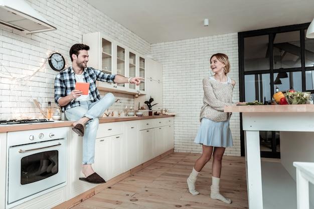 Gotowanie śniadania. młoda uśmiechnięta ładna kobieta z dużymi kolczykami wygląda na zadowoloną podczas przygotowywania śniadania