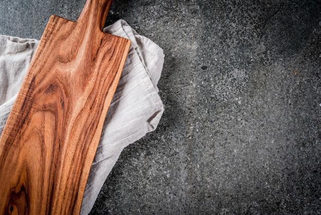 Gotowanie, stara drewniana deska do krojenia z ręcznikiem na czarnym kamiennym stole. widok z góry, lato