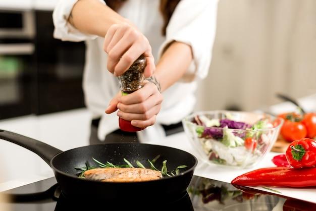 Gotowanie stek rybny z warzywami i przyprawami na patelni w kuchni. zdrowa żywność i żywienie