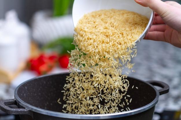 Gotowanie suchego złotożółtego długiego ryżu w rondlu na pyszne posiłki