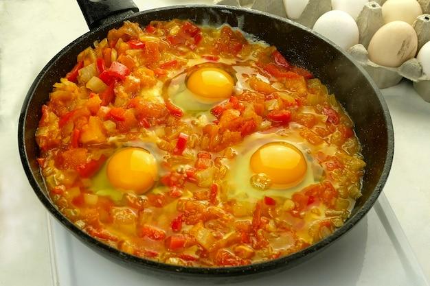 Gotowanie szakszuki z jajek sadzonych w sosie warzywnym na patelni. kuchnia żydowska i arabska.