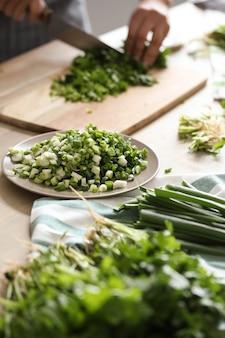 Gotowanie. szef kuchni kroi zieleninę w kuchni