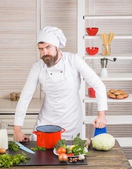 Gotowanie szefa kuchni w kuchni przystojny brodaty szef kuchni w jednolitych składnikach profesjonalna kuchnia zdrowa