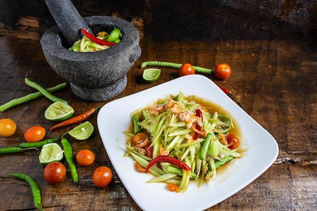 Gotowanie tajskie jedzenie, sałatka z papai i papaja sałatka w naczyniu z porcji na drewnianym stole.