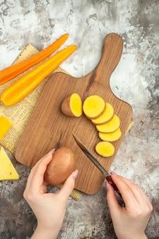 Gotowanie tła z różnymi warzywami i dwoma rodzajami noża do sera na drewnianej desce do krojenia