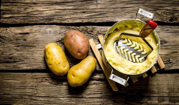 Gotowanie tłuczonych ziemniaków z tłuczkiem na podłoże drewniane