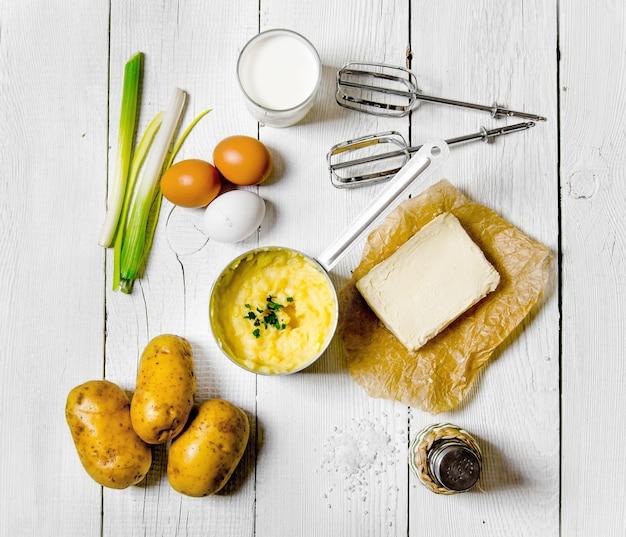 Gotowanie tłuczonych ziemniaków: ziemniaki, mleko, jajka, masło i inne na białym drewnianym stole.