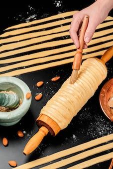 Gotowanie trdelnik. przysmak pieczony na szaszłyku i cieście węglowym z dodatkiem cukru, cynamonu i wanilii. świąteczne słodycze, uliczne jedzenie. kuchnia czeska i morawska.