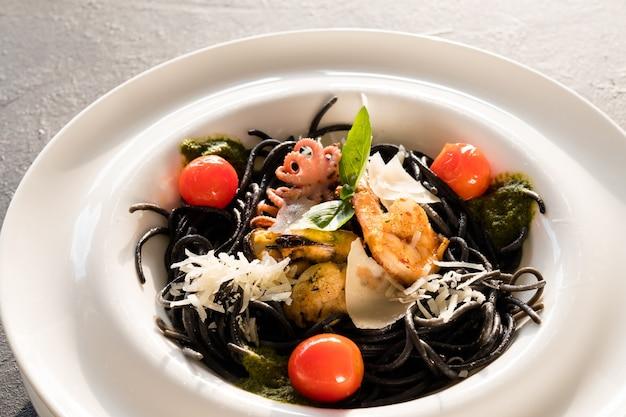 Gotowanie w restauracji. makaron z czarnym atramentem kalmara z kurczakiem i pomidorem.