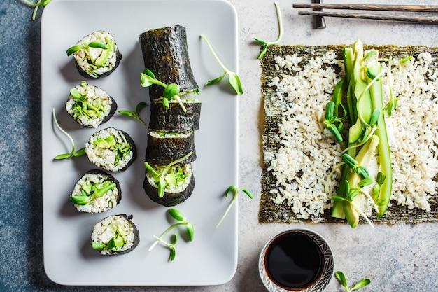 Gotowanie wegańskie rolki sushi z brązowym ryżem, awokado, ogórkiem, tofu i sadzonkami na szarym tle. pojęcie diety opartej na roślinach.