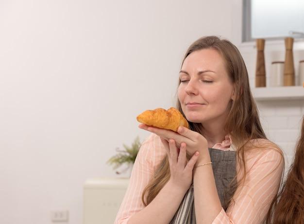 Gotowanie z mamą, szczęśliwa dziewczyna niosąca tacę i pachnąca świeżo ugotowanymi rogalikami, wnętrze kuchni, miejsce na kopię