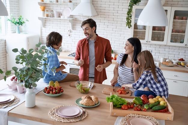 Gotowanie z rodzicami piękna urocza rodzina przygotowuje sałatkę wspólnie gotując w nowoczesnym stylu