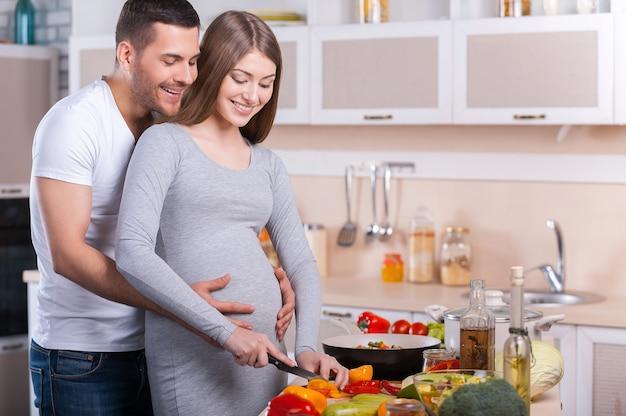 Gotowanie zdrowej żywności. szczęśliwa młoda para wspólnie gotuje w kuchni, podczas gdy mężczyzna dotyka brzucha swojej ciężarnej żony