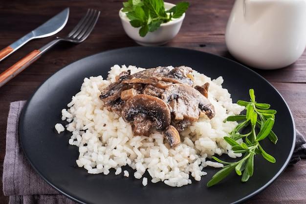 Gotowany biały ryż z grzybami w sosie śmietanowym.