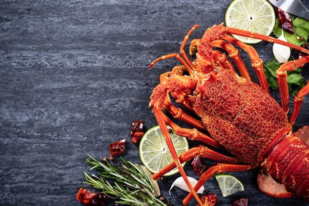 Gotowany homar, pyszny obiad z owocami morza zestaw z nożem i widelcem na tle czarnego kamienia łupka, projektowanie menu restauracji, widok z góry, nad głową