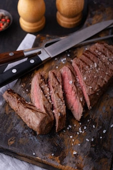 Gotowany i pokrojony stek wołowy na desce do krojenia
