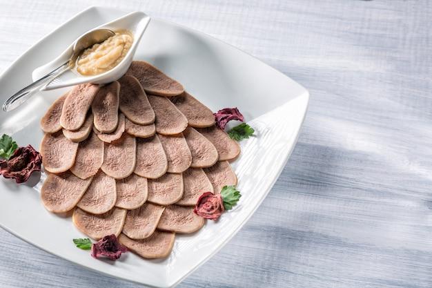 Gotowany język wołowy z chrzanem i ziołami na białym talerzu i drewnianym stole