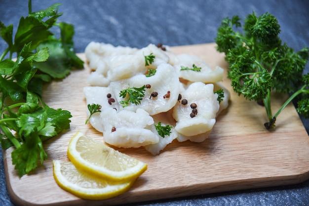 Gotowany kawałek ryby filet z cytryną i przyprawami na drewnianej desce do krojenia - pangasius dolly mięso z ryb