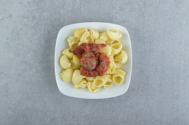 Gotowany makaron conchiglie z marynowanym mięsem na białym talerzu.