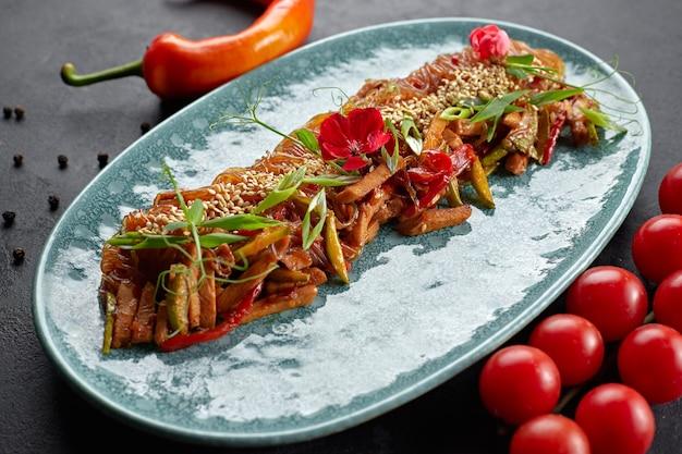 Gotowany makaron ryżowy z warzywami, sezamem, zieloną cebulą, pomidorkami koktajlowymi i ostrą czerwoną papryką na talerzu