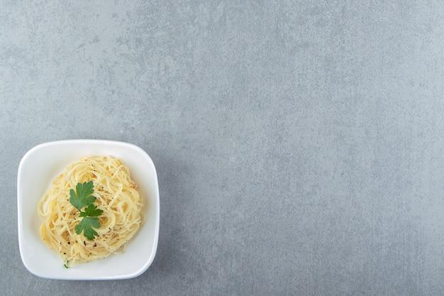Gotowany makaron spaghetti w białej misce.