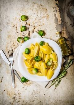 Gotowany makaron z brukselką na białym talerzu z oliwą z oliwek. na tle rustykalnym. widok z góry