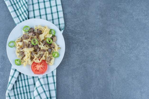 Gotowany makaron z kawałkami mięsa na białym talerzu.