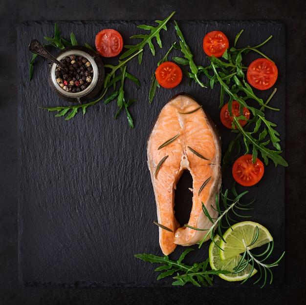 Gotowany na steaku z łososia z warzywami na czarnym stole. widok z góry