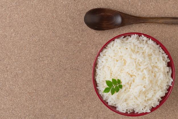 Gotowany ryż w czerwonej filiżance umieszczonej na sklejki.