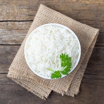 Gotowany ryż w misce na drewnianym stole w stylu rustykalnym.