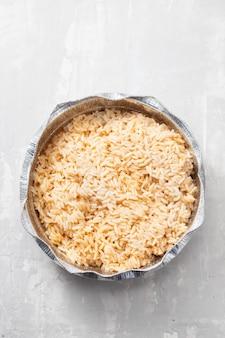 Gotowany ryż w pudełku na wynos na ceramicznym tle
