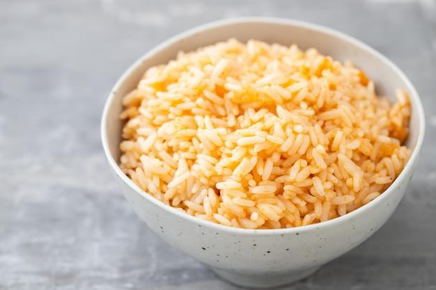 Gotowany ryż z pomidorami w misce na ceramicznym stole