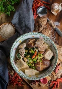 Gotowany ryż z wieprzowiną, kością porno i tajską kiełbasą wieprzową w misce