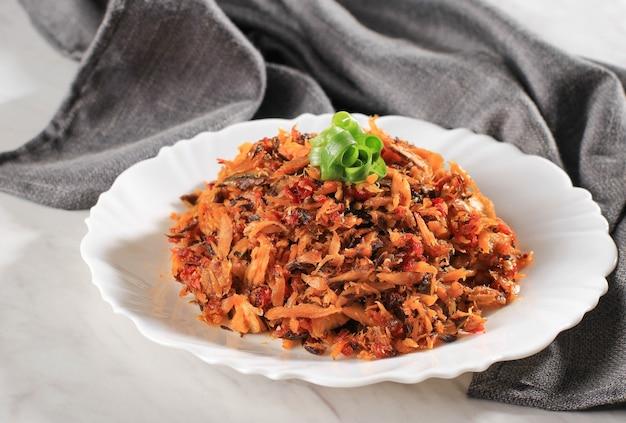 Gotowany solony tuńczyk z czerwonym sosem chili (balado tongkol suwir) na białym talerzu