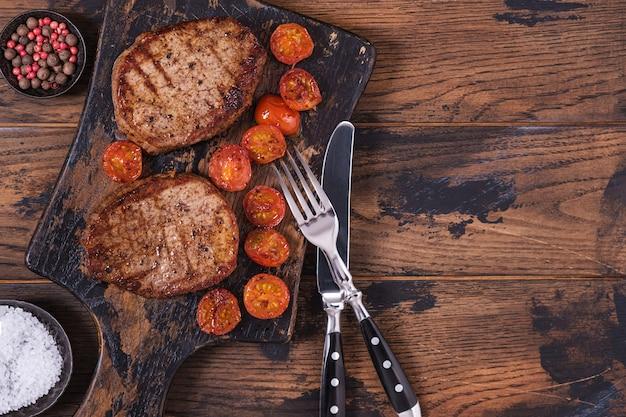 Gotowany stek wołowy z pomidorem na desce do krojenia
