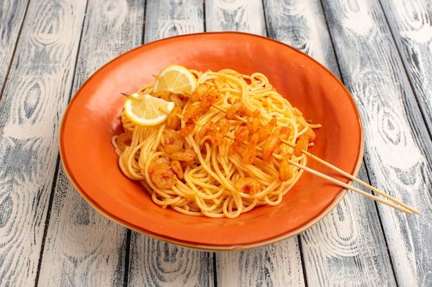 Gotowany włoski makaron smaczny z plasterkami cytryny i krewetkami wewnątrz pomarańczowego talerza na szaro