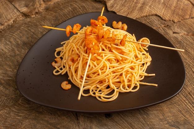 Gotowany włoski makaron z krewetkami wewnątrz brązowego talerza na drewnianym biurku
