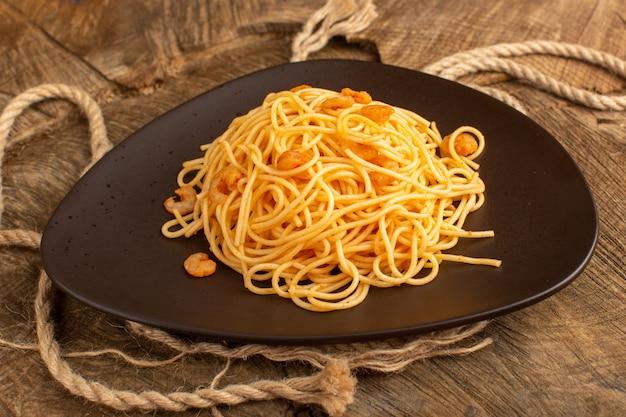 Gotowany włoski makaron z krewetkami wewnątrz brązowego talerza z linami na drewnianym biurku